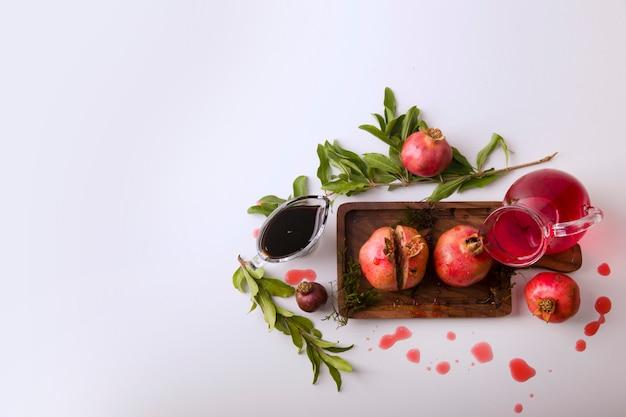 Granatäpfel mit roter soße und saft auf einem holzbrett, draufsicht