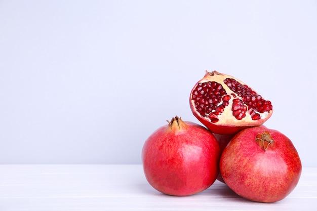 Granatäpfel und hälfte des reifen granatapfels auf einem grauen hintergrund