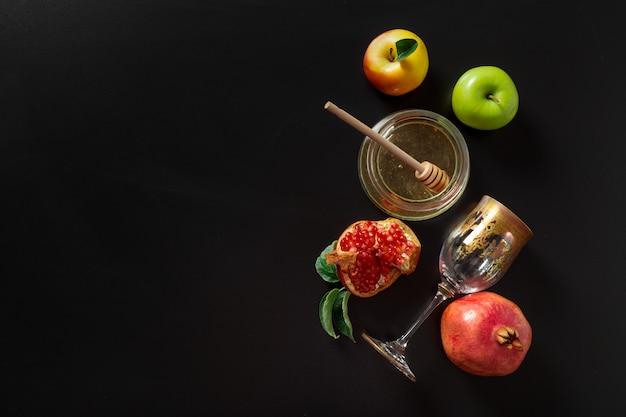 Granatapfel, apfel und honig für traditionelle feiertagssymbole rosh hashanah (jüdischer neujahrsfeiertag) auf schwarzem