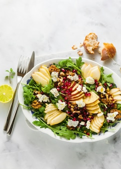 Granatapfel-birnen-grün-salat mit ingwer-dressing auf weißem marmor. gesundes frühstück oder mittagessen