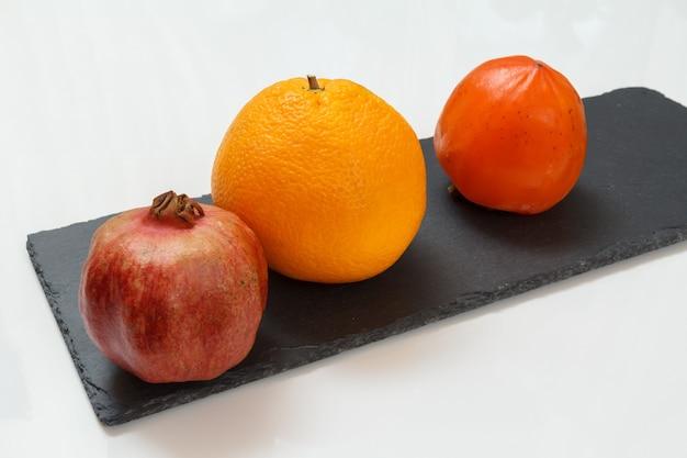 Granatapfel, eine orange und eine reife kakifrucht auf dem schwarzen steinbrett und weißem hintergrund. bio-früchte.