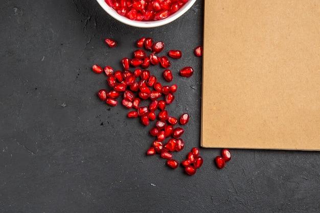 Granatapfel-granatapfel-samen von oben in der nahtansicht im schüssel-sahne-notizbuch