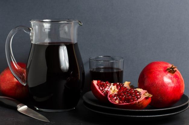 Granatapfel, granatapfelsaft in einer glasschale. dunkler hintergrund. seitenansicht. kopieren sie platz