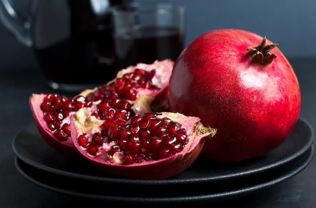Granatapfel, granatapfelsaft in einer glasschale. dunkler hintergrund. seitenansicht.