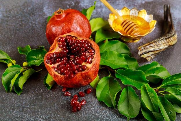 Granatapfel mit samen, honig und horn für den jüdischen feiertag rosh hashanah