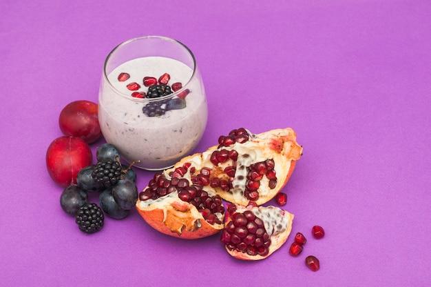 Granatapfel; trauben; pflaumen- und brombeerensmoothies auf lila hintergrund