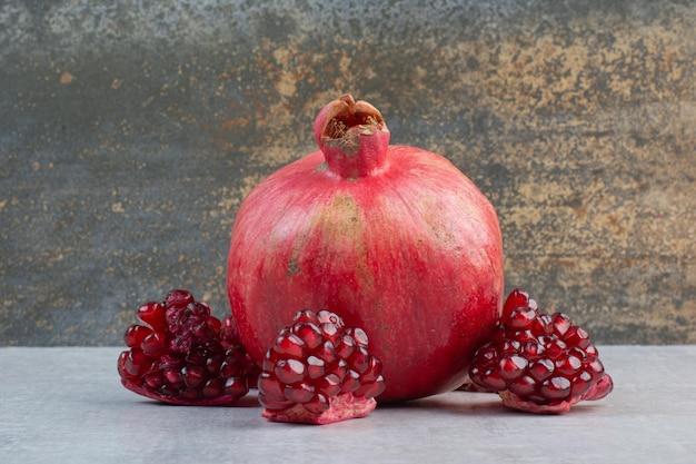 Granatapfel und granatapfelkerne auf steintisch. foto in hoher qualität