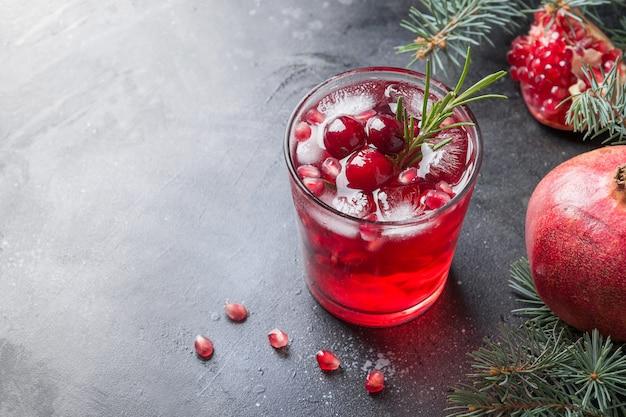 Granatapfel-weihnachtscocktail mit rosmarin-champagner-club-soda auf schwarz