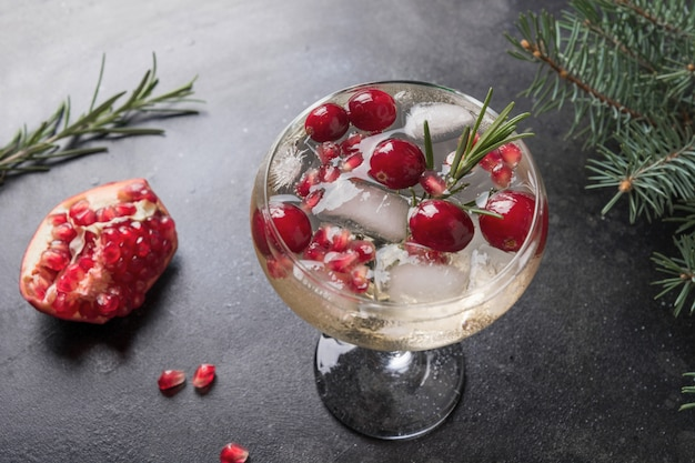 Granatapfel-weihnachtscocktail mit rosmarin, champagner, vereinsoda auf schwarzem. nahansicht.