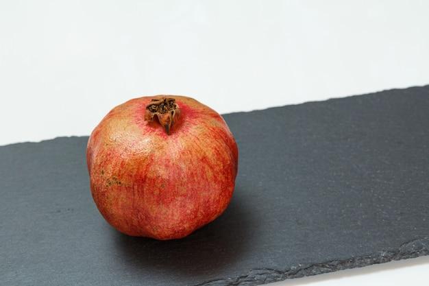 Granatapfelfrucht auf dem schwarzen steinbrett und weißem hintergrund. bio-früchte.