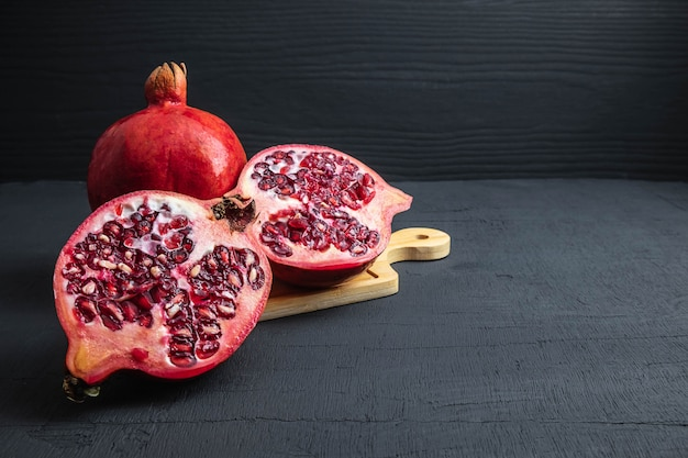 Granatapfelfrucht geschnitten auf schwarzem hintergrund