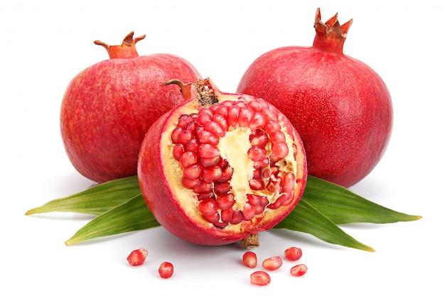 Granatapfelfrüchte mit grünem blatt und schnitten lokalisiert
