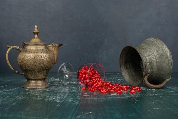 Granatapfelkerne auf marmortisch mit vase und teekanne verstreut.