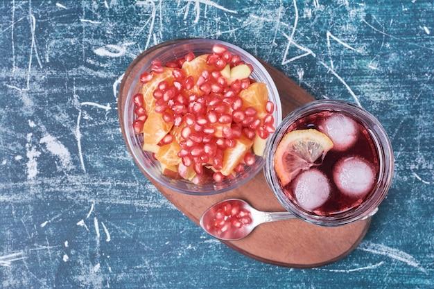 Granatapfelkerne mit einer tasse getränk auf blau.