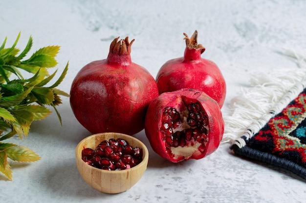 Granatapfelkerne mit ganzen oder geschnittenen granatäpfeln auf grauer wand.