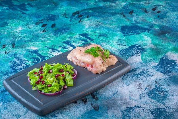 Granatapfelkerne, salatblätter mit zwiebelring neben hähnchenbrust auf einem holztablett