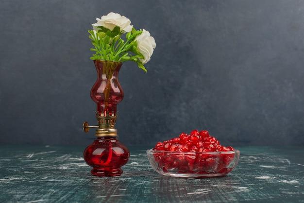 Granatapfelkerne und weiße blüten in der vase.