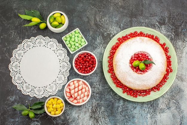 Granatapfelkuchen mit granatapfelkernenspitzendeckchen schalen mit limetten bonbons