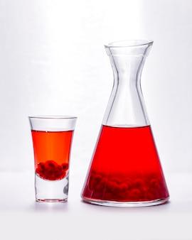 Granatapfelsaft im schnapsglas und krug mit samen in der seitenansicht