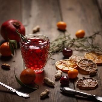 Granatapfelsaft mit granatäpfeln und trockenfrüchten auf einem holztisch. landhausstil.