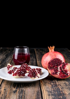 Granatapfelsaft und granatapfel auf holztisch