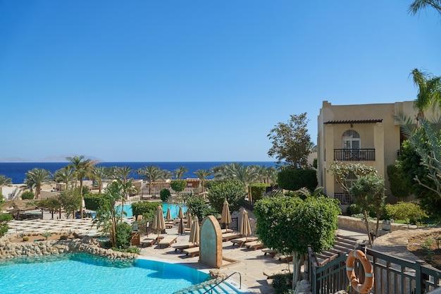 Grand hotel mit palmen und swimmingpool im sommer