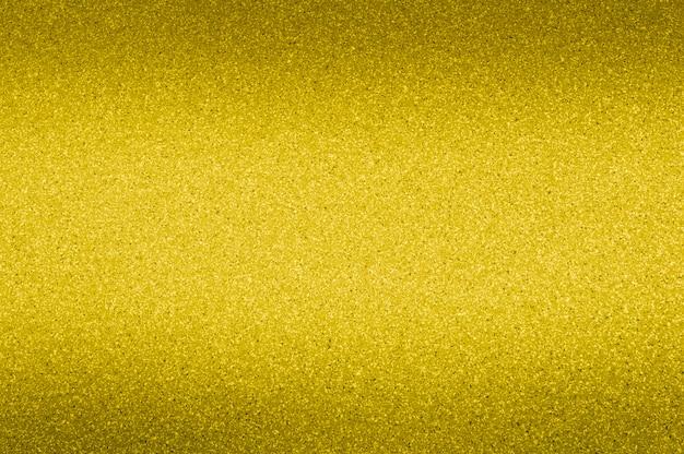 Granithintergrund der goldenen farbe mit kleinen punkten. verdunkelung von oben und unten.