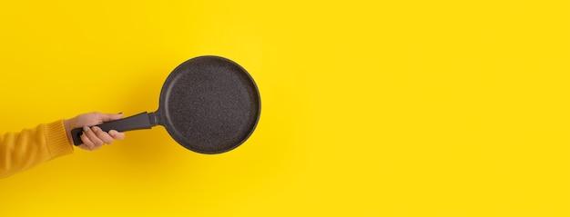 Granitpfanne für pfannkuchen in der hand über gelbem hintergrund, panoramabild
