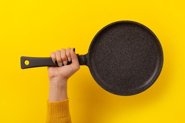 Granitpfanne für pfannkuchen in der hand über gelbem hintergrund