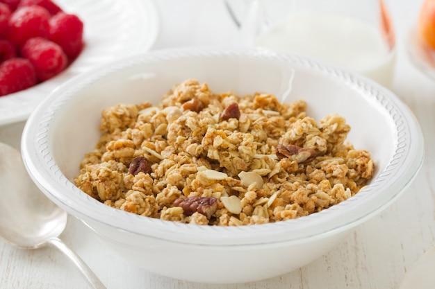 Granola in der weißen schüssel mit milch und früchten auf weißer holzoberfläche