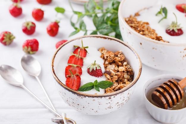 Granola mit frischen erdbeeren gesundes frühstück des sommers.