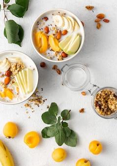 Granolafrühstück mit früchten, nüssen, milch und erdnussbutter in der schüssel. draufsicht des gesunden frühstückskost aus getreide