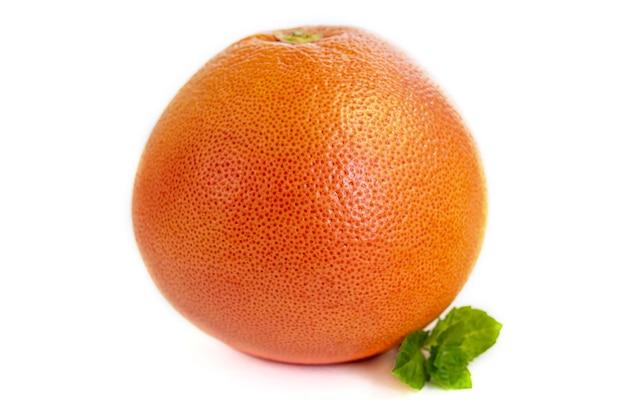 Grapefruit auf einem weißen teller mit einem zweig minze. isolieren. platz kopieren.