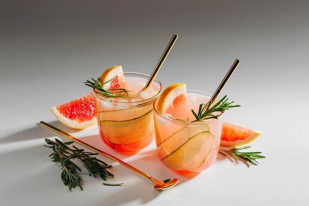 Grapefruit-gurken-gin-cocktail auf eleganten gläsern auf weißem hintergrund mit schatten