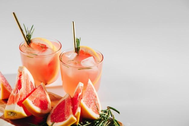 Grapefruit-gurken-gin-cocktail auf eleganten gläsern auf weißem hintergrund