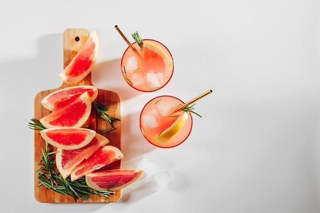 Grapefruit-gurken-gin-cocktail auf gläsern und einem holzbrett auf weißem hintergrund