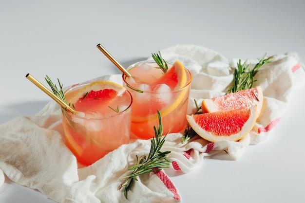 Grapefruit-gurken-gin-cocktail auf gläsern und einem weißen tuch auf weißem hintergrund