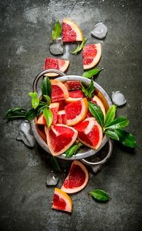Grapefruit in einen topf mit blättern und eis auf einem steintisch schneiden. draufsicht