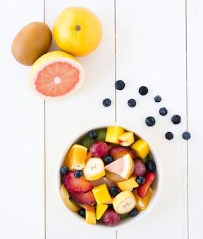 Grapefruit; kiwi und blaubeeren mit schüssel fruchtsalat auf weißem schreibtisch aus holz