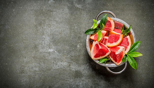 Grapefruit mit blättern in einen topf auf steintisch schneiden. draufsicht