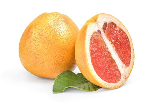 Grapefruit mit halbem und grünem blatt isoliert auf weißem oberflächenausschnitt.