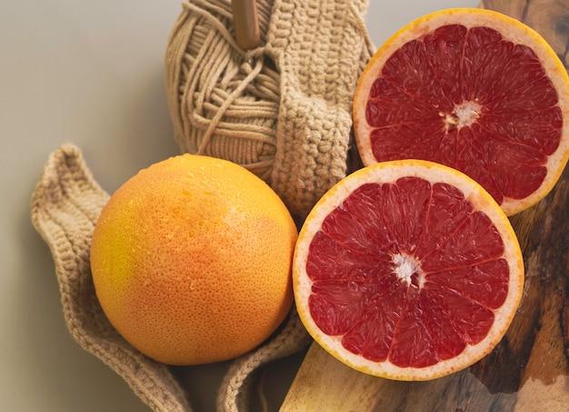 Grapefruit mit orangenschale und rosa fruchtfleisch auf den hintergrund gelegt, verschwommenes licht herum