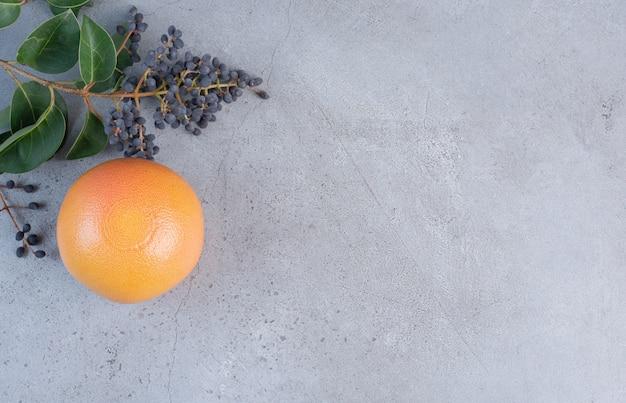 Grapefruit neben dekorativem zweig mit beeren und blättern auf marmorhintergrund.