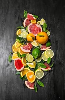 Grapefruit, orange, mandarine, zitrone, limette auf schwarzem holztisch. draufsicht