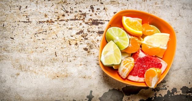 Grapefruit, orange, mandarine, zitrone, limette in der tasse auf rustikalem tisch. draufsicht