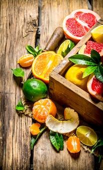 Grapefruit, orange, mandarine, zitrone, limette in einer alten schachtel auf holztisch.