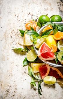 Grapefruit, orange, mandarine, zitrone, limette in einer tasse mit blättern auf rustikalem tisch.