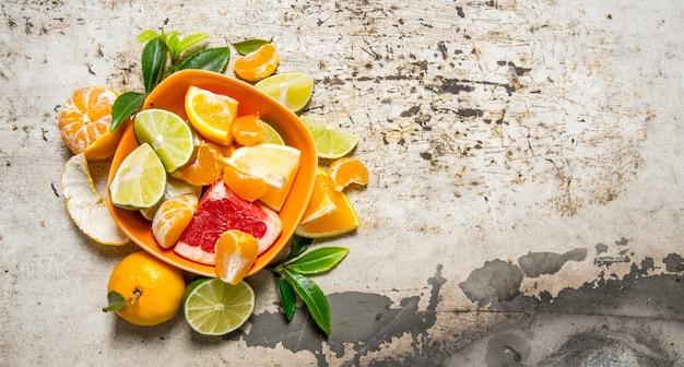 Grapefruit, orange, mandarine, zitrone, limette in tasse auf rustikalem tisch. draufsicht