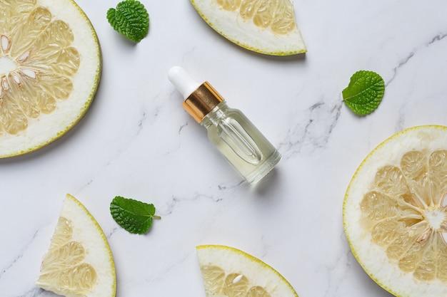 Grapefruitöl-serumflasche auf weißem marmorhintergrund