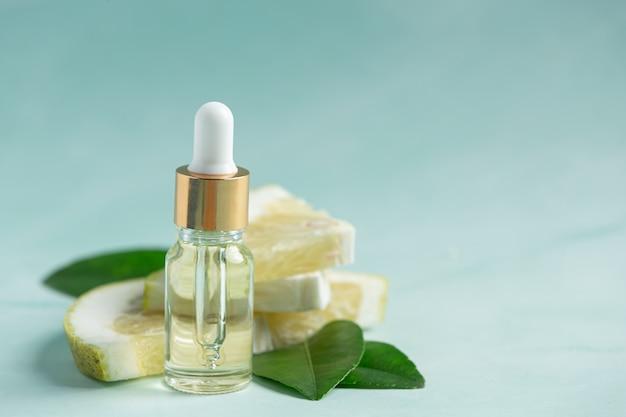 Grapefruitöl-serumflasche setzte auf grünes lichthintergrund